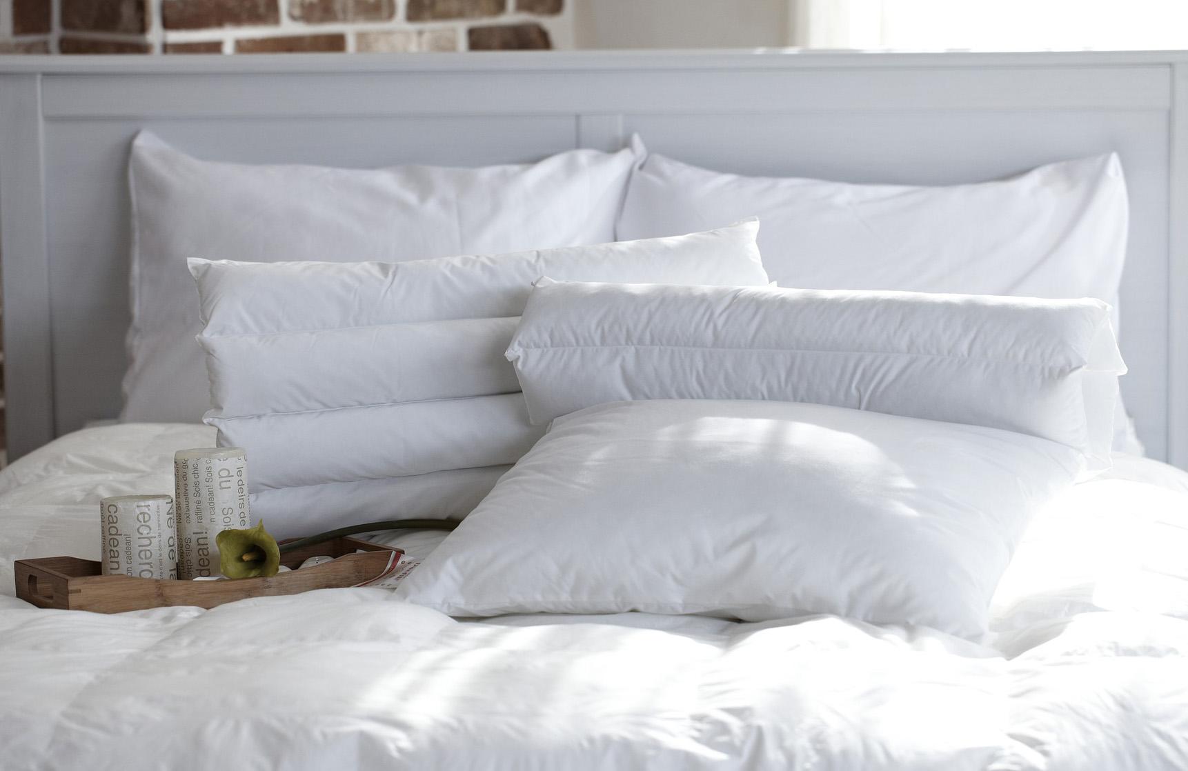 mehrere Kopfkissen im Bett