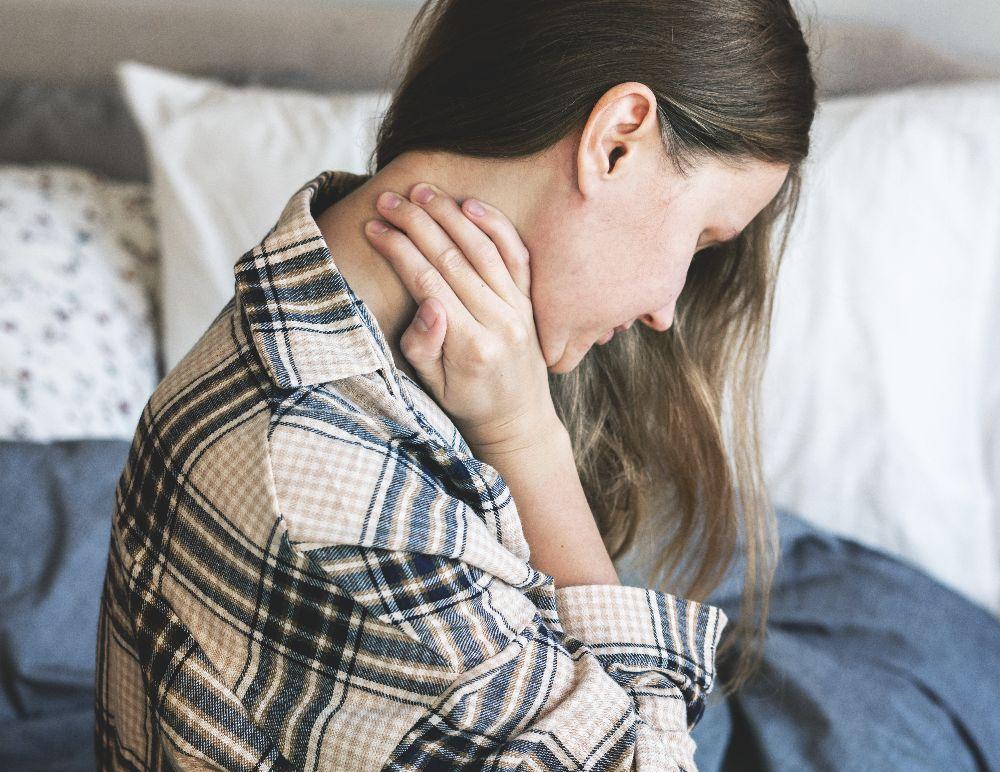 Frau hält sich Nacken Schmerzen